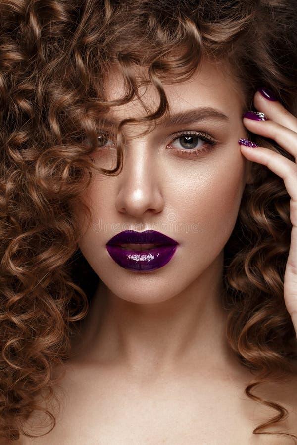 有晚上构成的美丽的女孩,紫色嘴唇、卷毛和设计修剪钉子 秀丽表面 库存照片