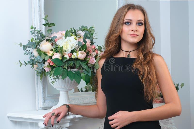 有晚上构成的美丽的妇女在黑礼服 免版税库存照片
