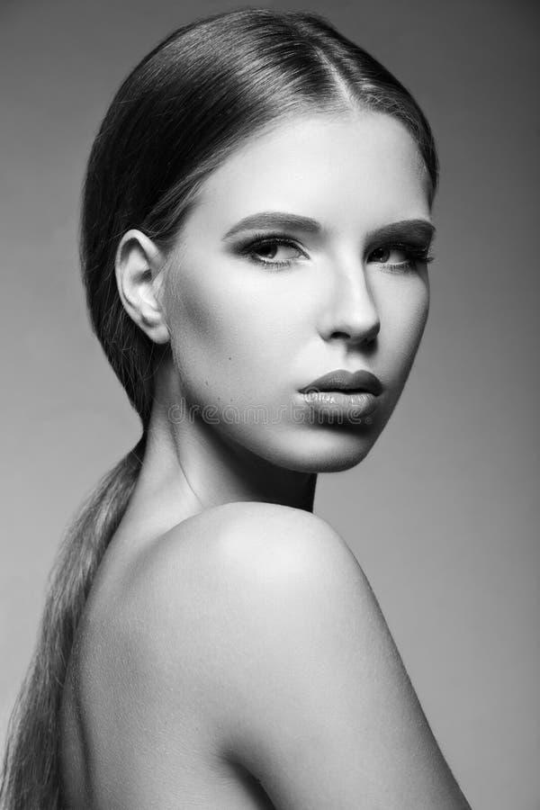 有晚上构成的美丽的妇女,长的直发 注视发烟性 床单方式放置照片诱人的白人妇女年轻人 黑色白色 图库摄影