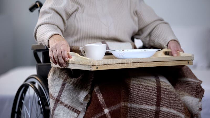 有晚餐的,护理上门服务,康复中心老残疾妇女藏品盘子 库存照片