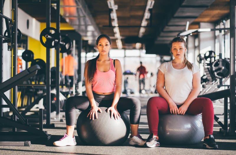有普拉提从他们的锻炼的球或健身房球的两个健康女孩休假在健身房 免版税库存图片