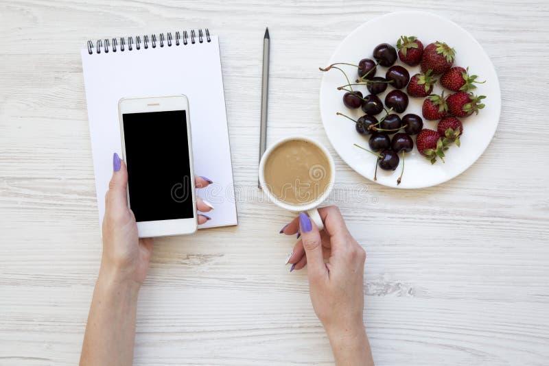 有智能手机、拿铁、笔记本、草莓和樱桃的妇女手在白色木背景,顶视图 库存照片