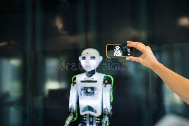 有智能手机和机器人的无法认出的科学家 免版税库存图片