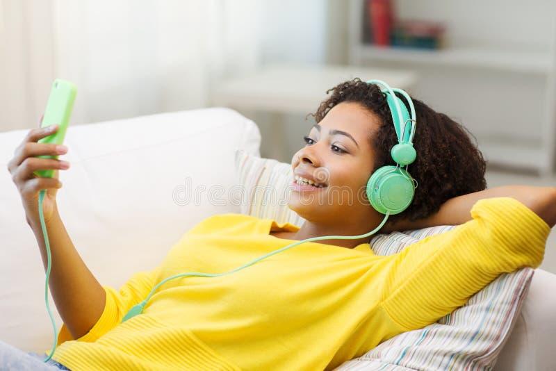 有智能手机和耳机的愉快的非洲妇女 免版税库存图片