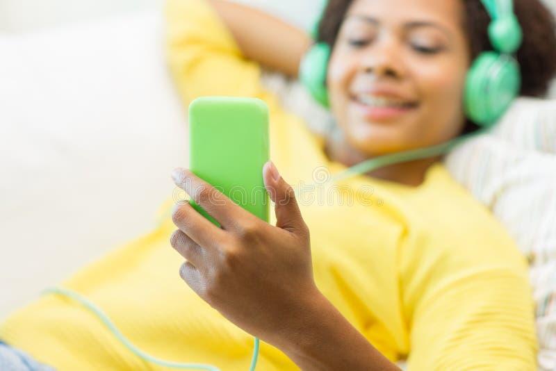 有智能手机和耳机的愉快的非洲妇女 图库摄影