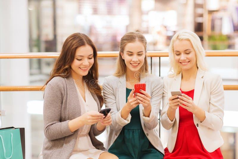有智能手机和购物袋的愉快的妇女 免版税库存图片