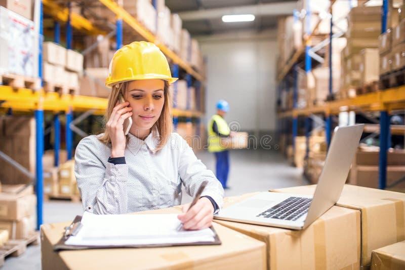 有智能手机工作的年轻仓库工作者 免版税库存图片