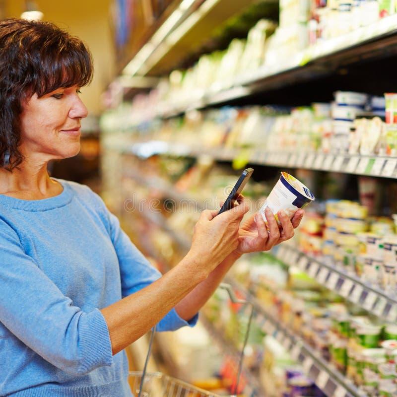 有智能手机扫描条形码的妇女在超级市场 库存照片