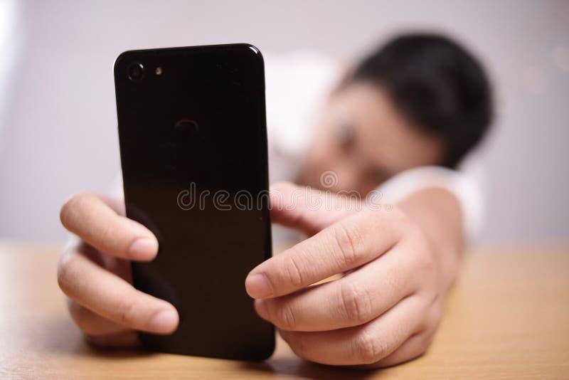 有智能手机担心的表示的哀伤的人 免版税库存图片