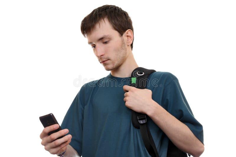 有智能手机的一个年轻沉思人 库存图片