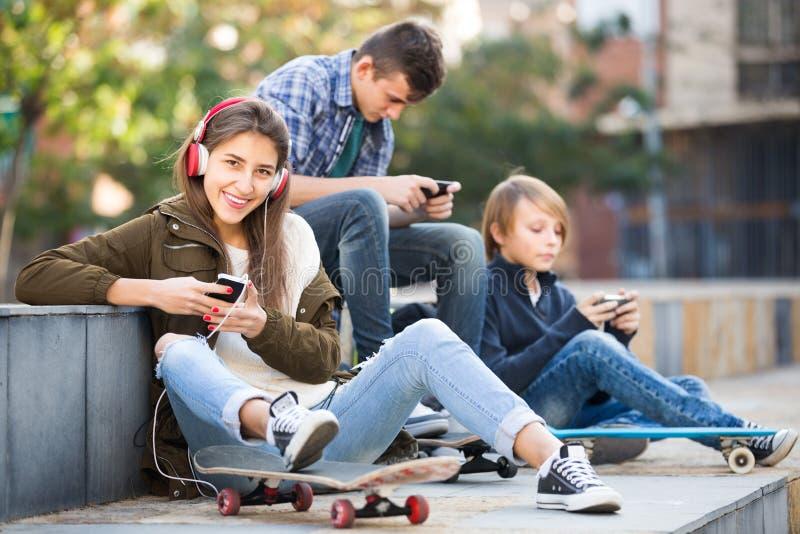 有智能手机的三个少年 免版税库存图片