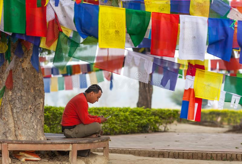 有智能手机的人在佛教prayful旗子下 免版税库存图片