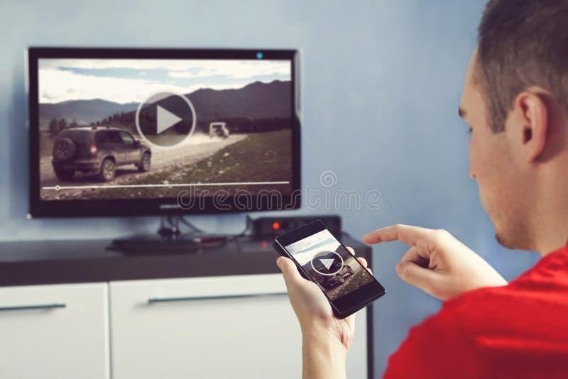 有智能手机的人在家被连接到A电视观看的录影 免版税库存图片