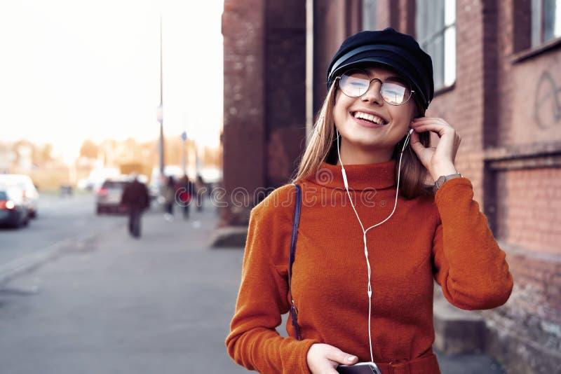有智能手机的俏丽的笑的女孩有一美好时光在秋天周末 讨人喜欢的时髦夫人室外画象与 免版税图库摄影