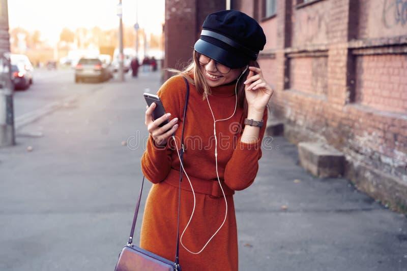 有智能手机的俏丽的笑的女孩有一美好时光在秋天周末 讨人喜欢的时髦夫人室外画象与 免版税库存照片