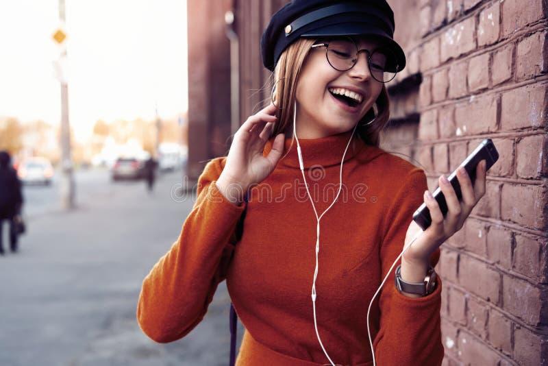 有智能手机的俏丽的笑的女孩有一美好时光在秋天周末 讨人喜欢的时髦夫人室外画象与 库存照片