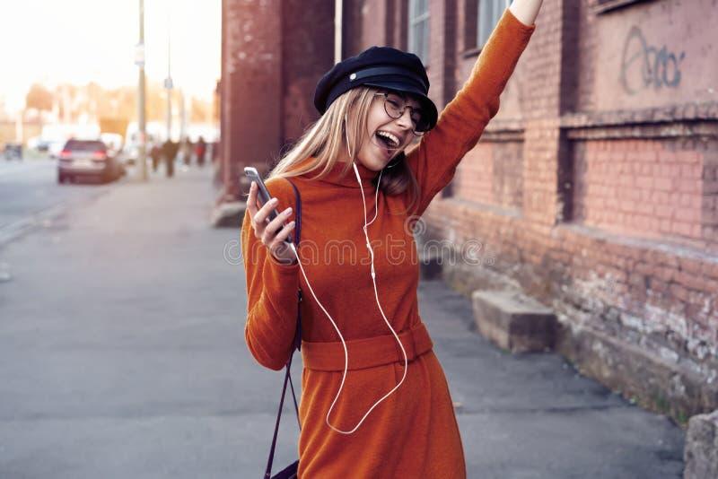 有智能手机的俏丽的笑的女孩有一美好时光在秋天周末 讨人喜欢的时髦夫人室外画象与 库存图片