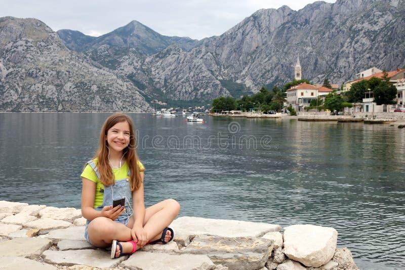 有智能手机的十几岁的女孩在暑假科托尔海湾黑山 免版税库存图片