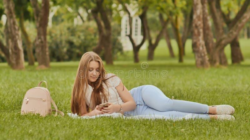 有智能手机的可爱的女孩学生在草公园说谎 在研究期间的休息 库存照片