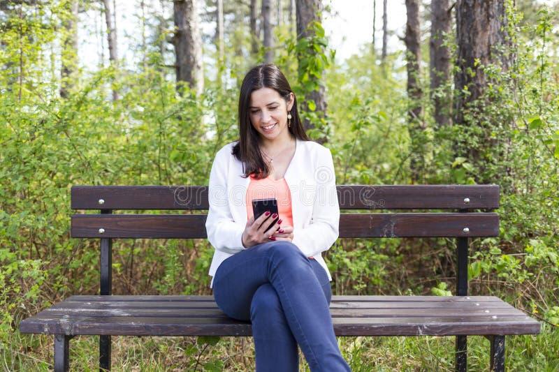有智能手机的可爱的微笑的少妇在公园 免版税库存照片