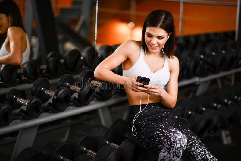 有智能手机的听到在健身房的音乐的年轻女运动员画象  库存图片