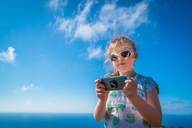 有智能手机的女孩在海滩 免版税图库摄影