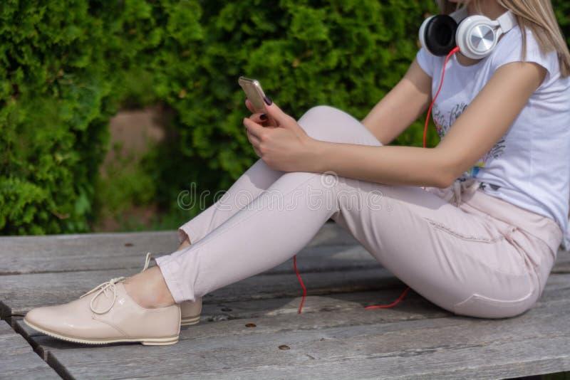 有智能手机的女孩在腿和耳机在脖子上坐一条长凳在公园和休息 免版税库存图片