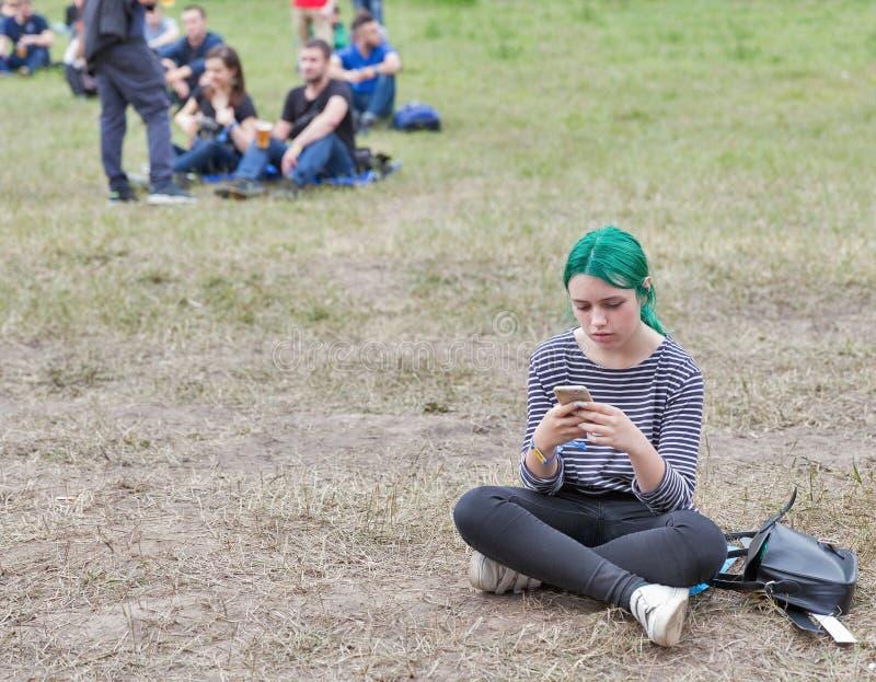 有智能手机的女孩 地图集周末节日在基辅,乌克兰 免版税库存图片