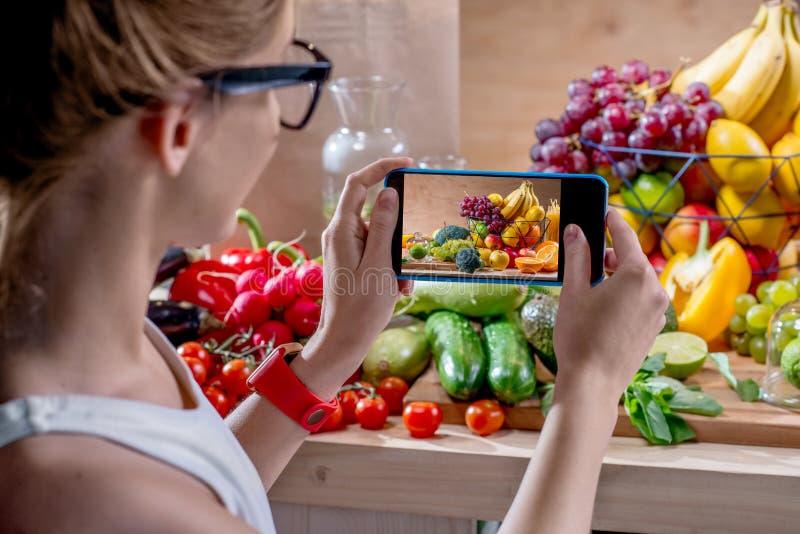 有智能手机的女性食物摄影师 免版税图库摄影
