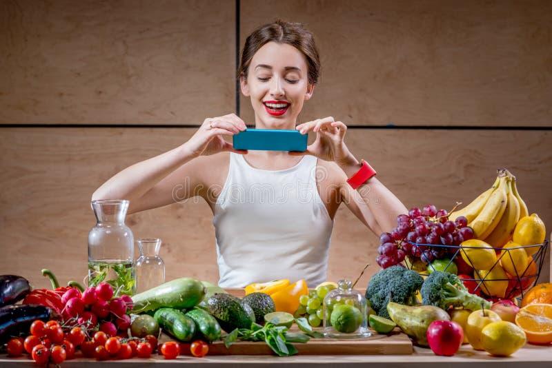 有智能手机的女性食物摄影师 免版税库存图片