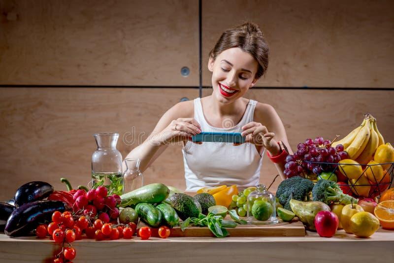 有智能手机的女性食物摄影师 免版税库存照片