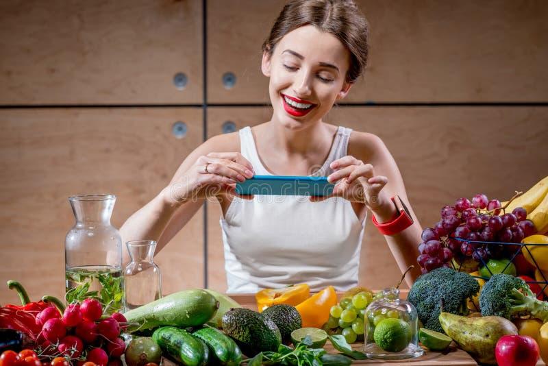 有智能手机的女性食物摄影师 库存图片