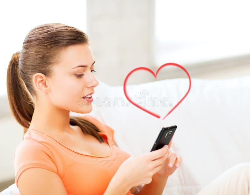 有智能手机的妇女在家 免版税库存照片
