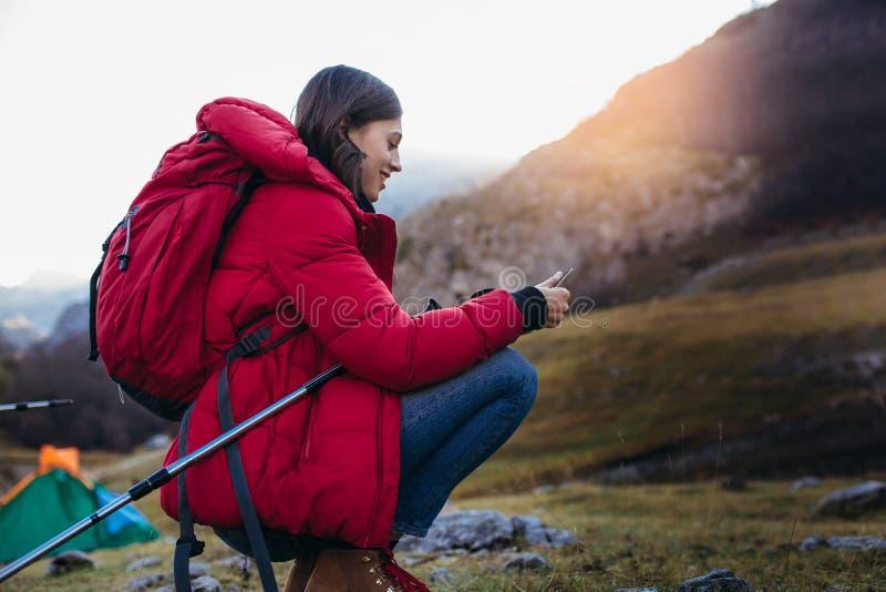 有智能手机的妇女徒步旅行者在日落的山峰峭壁 免版税库存图片