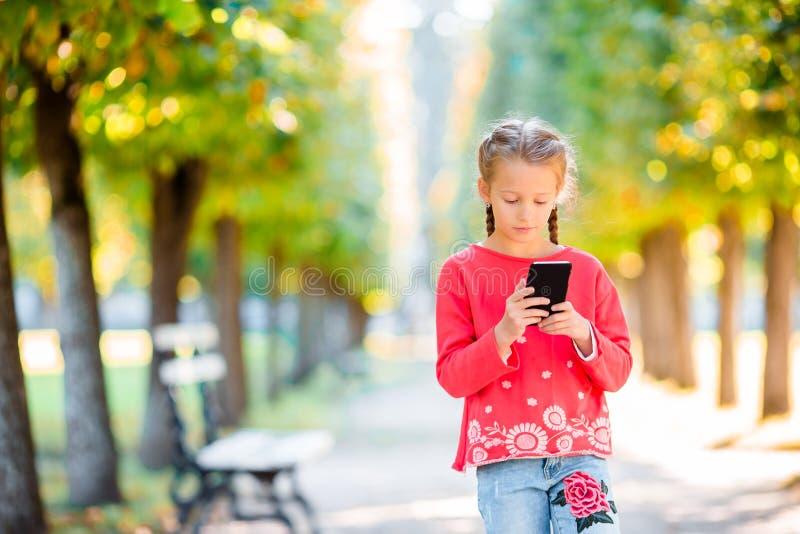 有智能手机的小可爱的女孩在秋天 库存图片