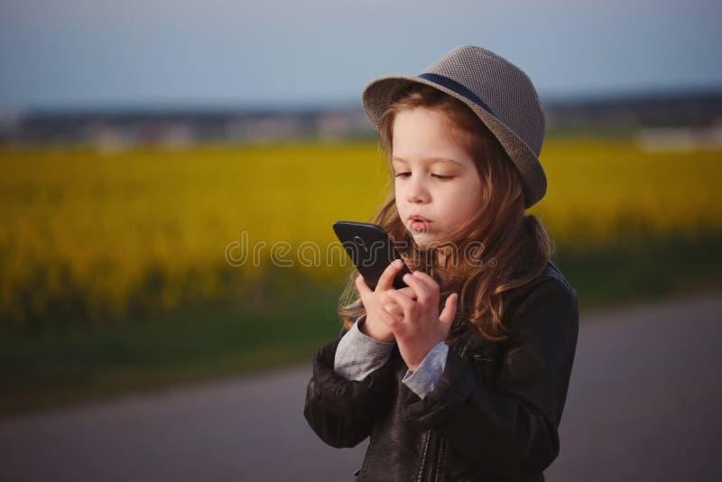 有智能手机的小滑稽的女孩 免版税图库摄影