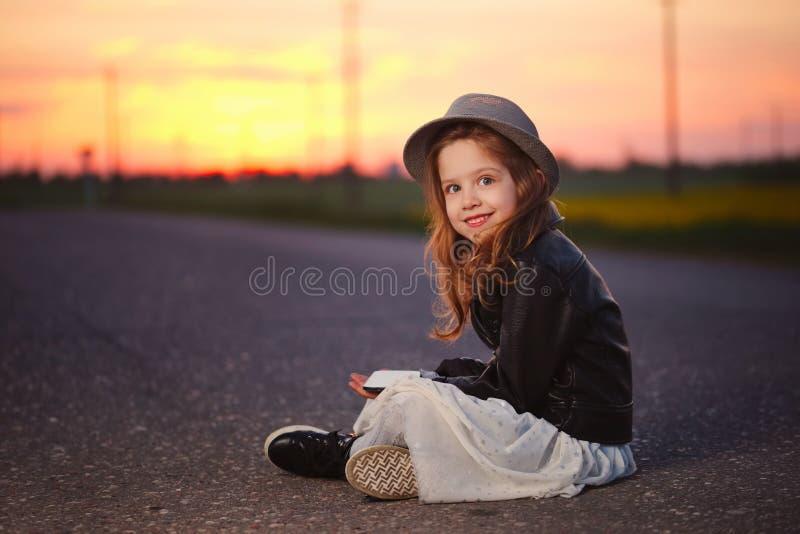 有智能手机的小滑稽的女孩 免版税库存图片