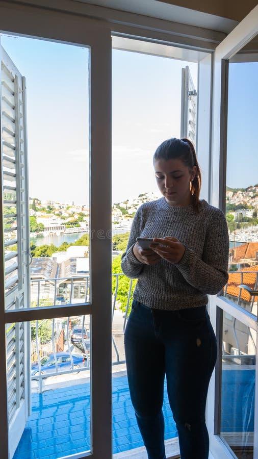 有智能手机的少女在有阳台的一间屋子里 有灰色长的衬衣的红色顶头妇女 白色木窗帘和门 免版税图库摄影