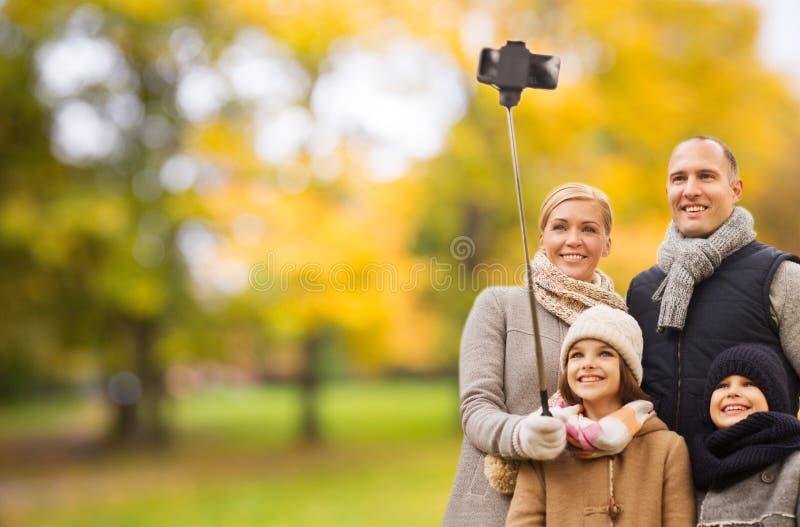 有智能手机的幸福家庭和monopod在公园 免版税库存图片