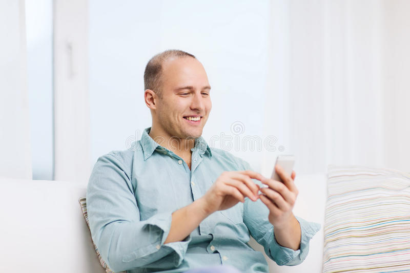 有智能手机的微笑的人在家 免版税库存图片
