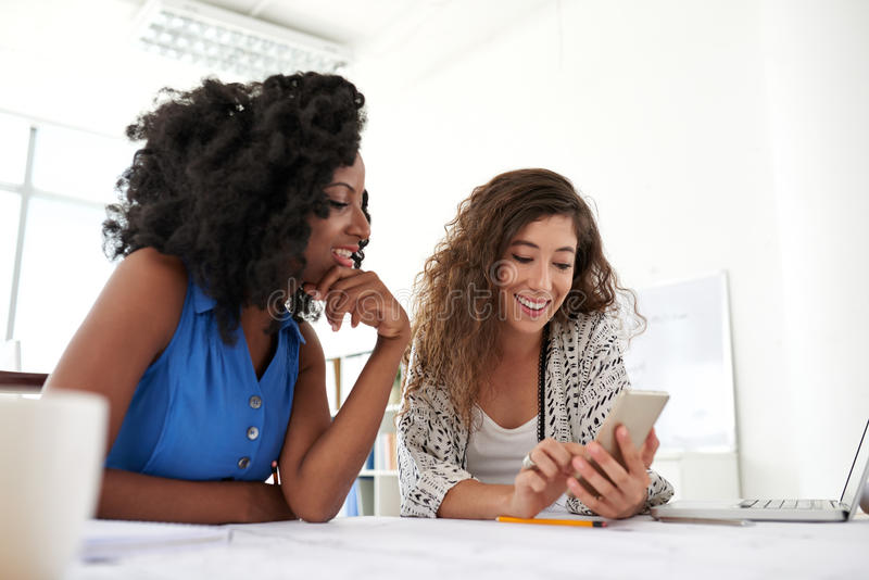 有智能手机的微笑的工友 免版税库存图片