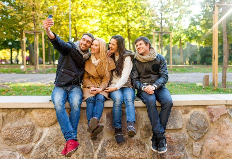 有智能手机的微笑的朋友在城市公园 免版税图库摄影