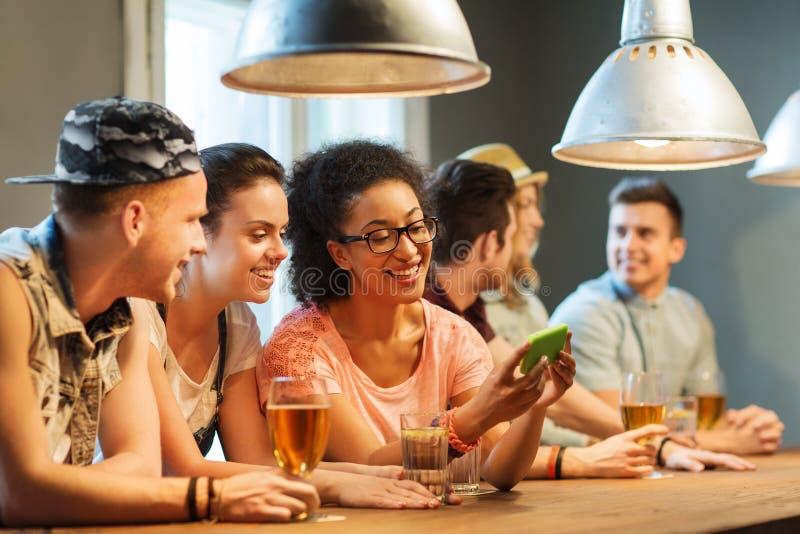 有智能手机的愉快的在酒吧的朋友和饮料 免版税图库摄影