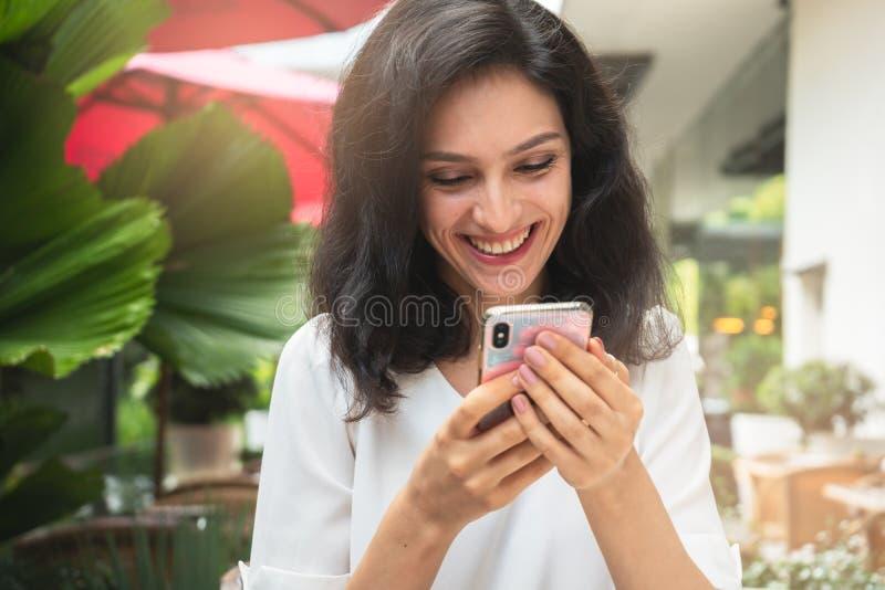 有智能手机的愉快的妇女在一个餐馆大阳台有未聚焦的背景 免版税图库摄影