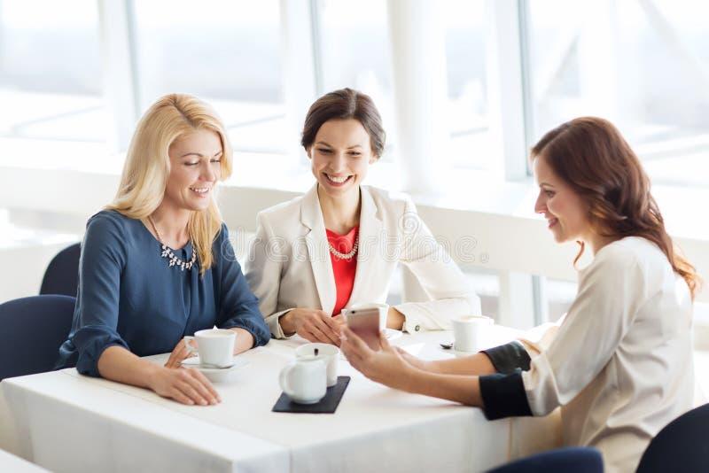 有智能手机的愉快的妇女在餐馆 免版税库存照片