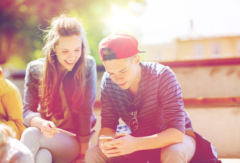 有智能手机的愉快的少年朋友户外 免版税库存照片