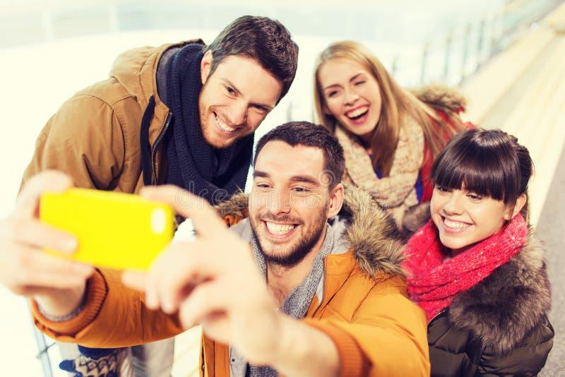 有智能手机的愉快的朋友在滑冰场 免版税库存图片
