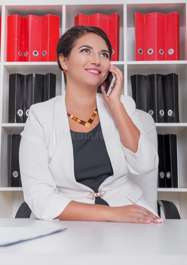 有智能手机的愉快的现代美丽的女商人 免版税库存图片