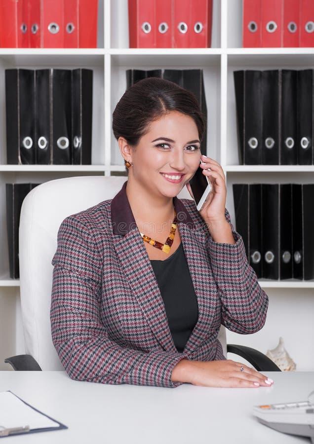 有智能手机的愉快的美丽的女商人在办公室 库存照片