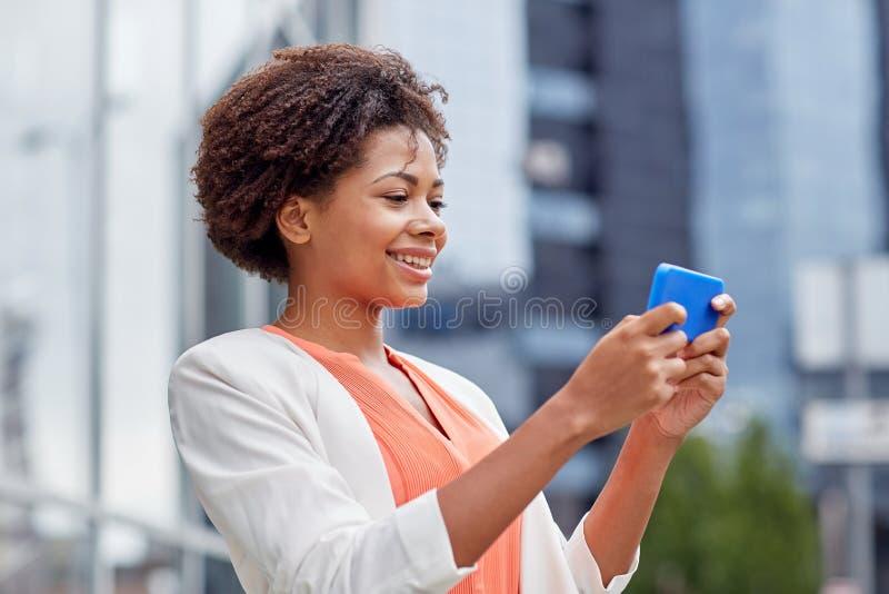 有智能手机的愉快的非洲女实业家 免版税库存图片